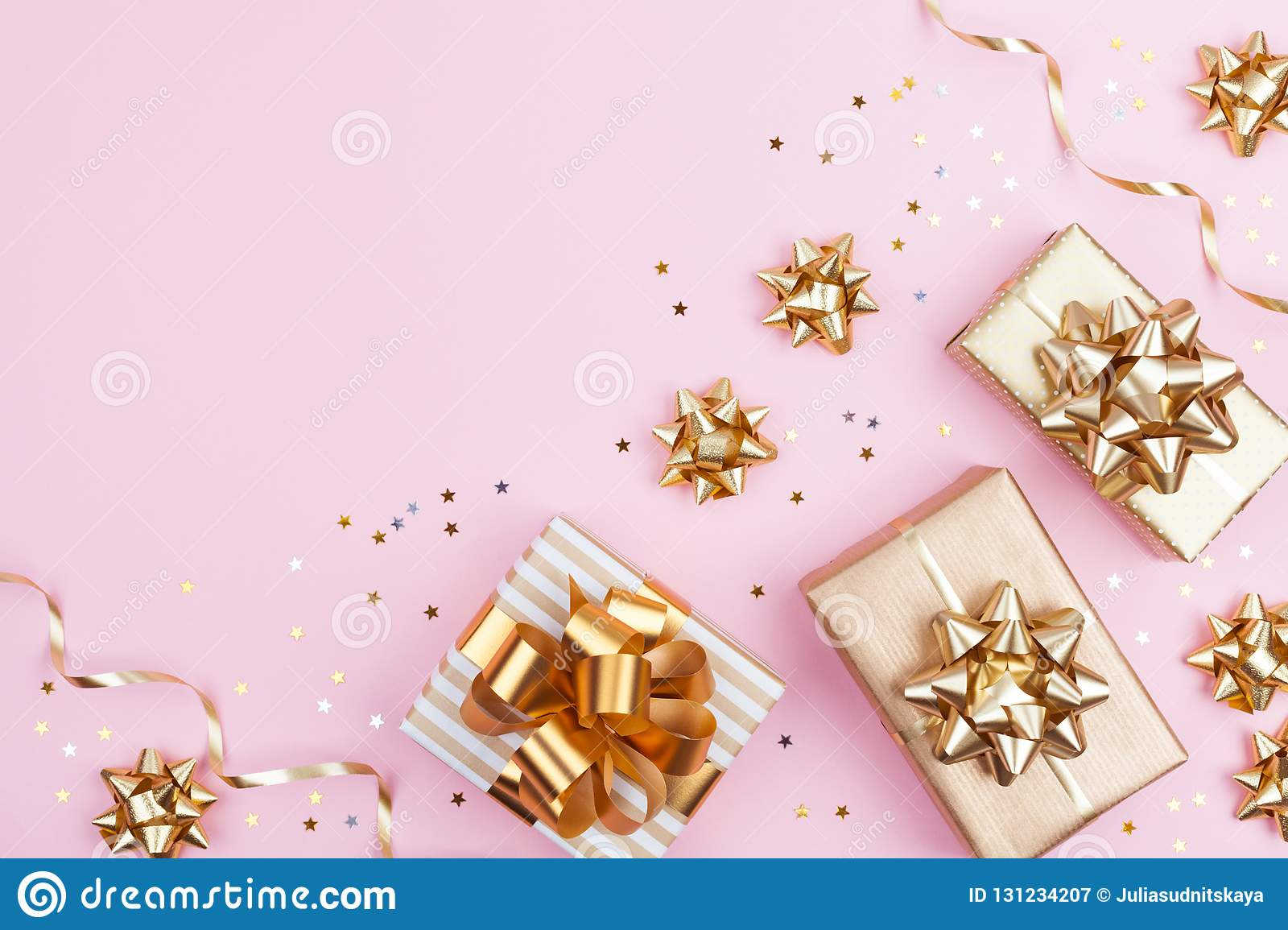 Fashion gifts or presents boxes with golden bows and star confetti on pink pastel background top view. Flat lay for Christmas