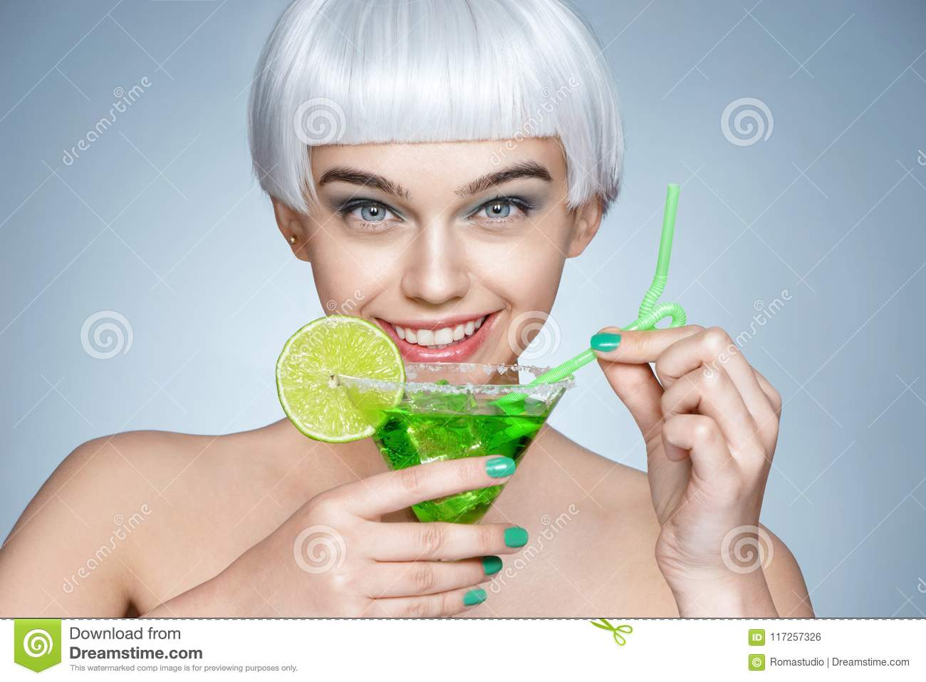 Fashion girl with glass of cocktail on blue background