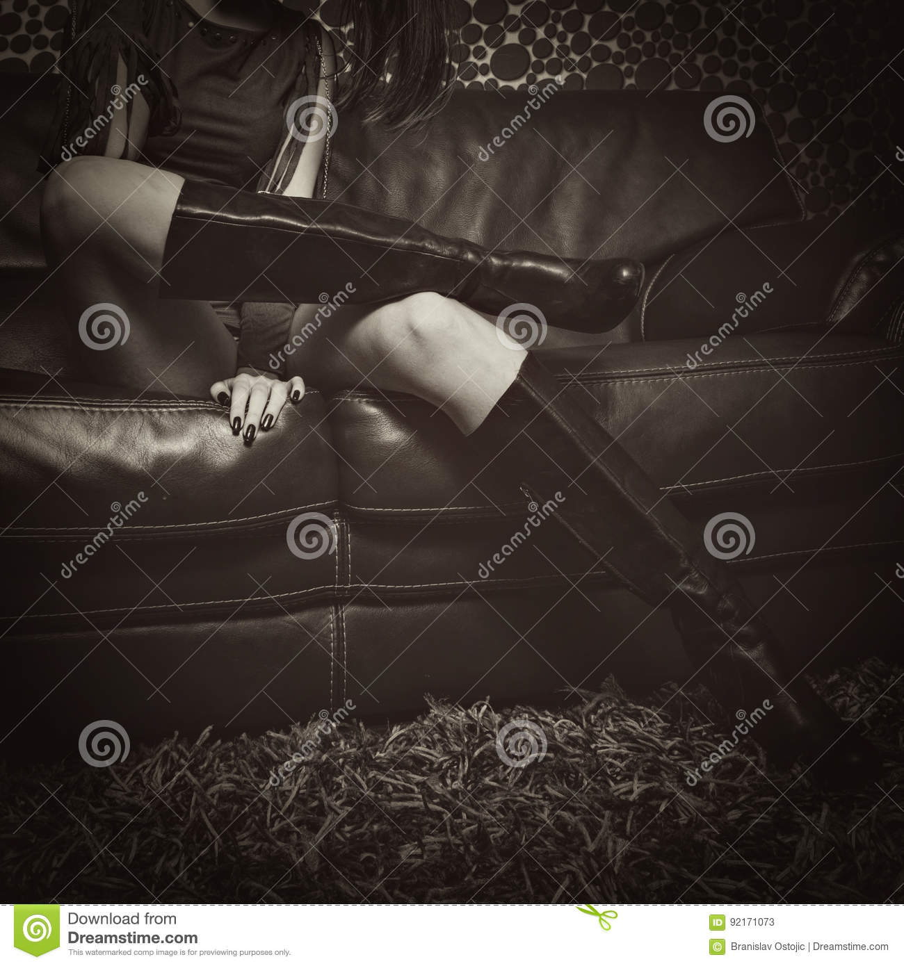Fashion girl in high heel boots on leather sofa