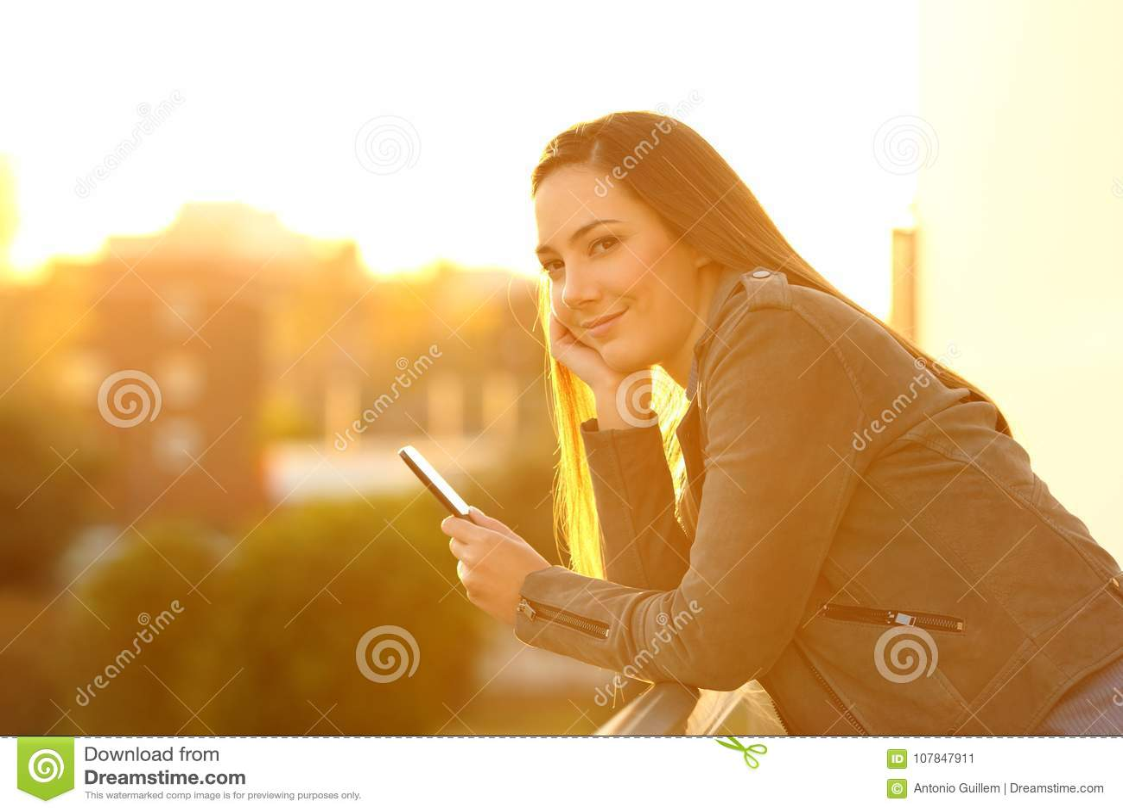 Fashion girl holding a phone looking at camera at sunset