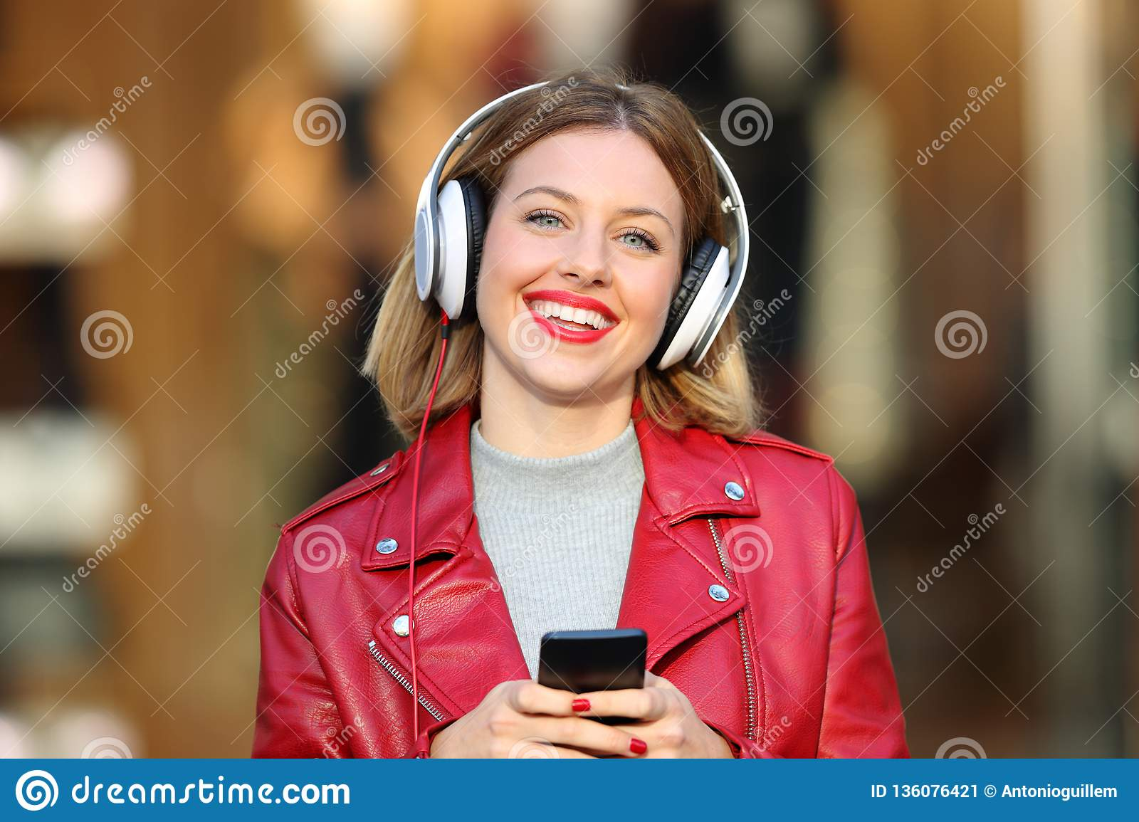 Fashion girl listening to music from phone looking at you