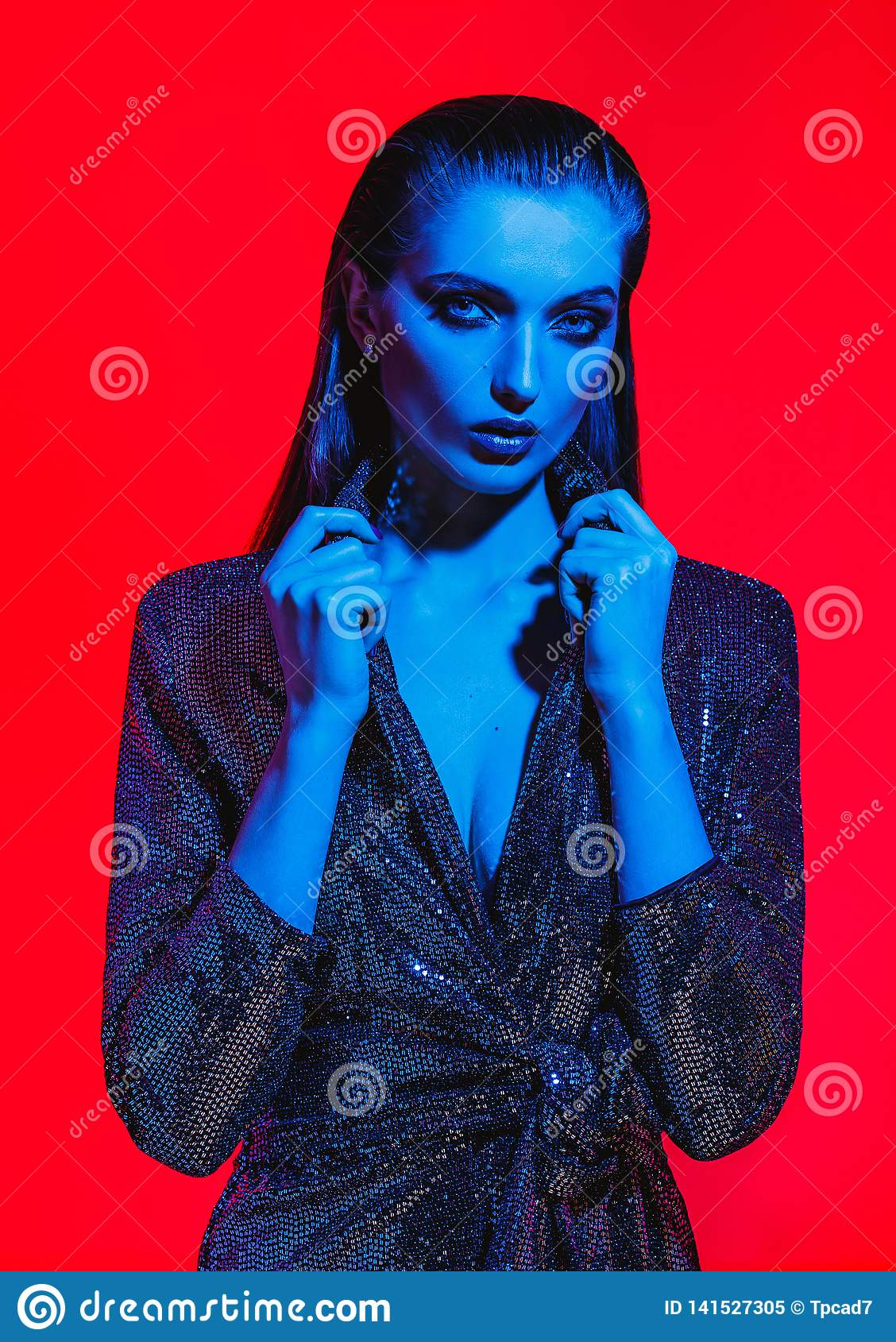 Fashion girl with long hair and stylish makeup in a black shining dress poses on the red background in neon light in the