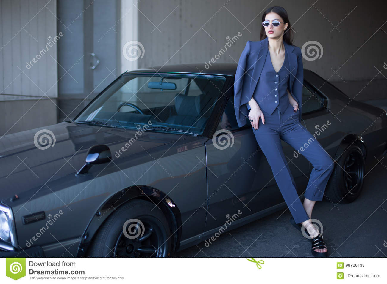 Fashion girl standing next to a retro sport car on the sun. Stylish woman in a gray suit waiting near classic car