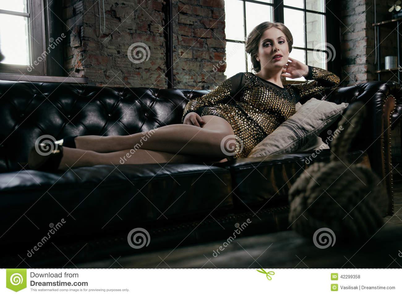 Fashion Glamour Girl Lying On A Black Leather Sofa Stock