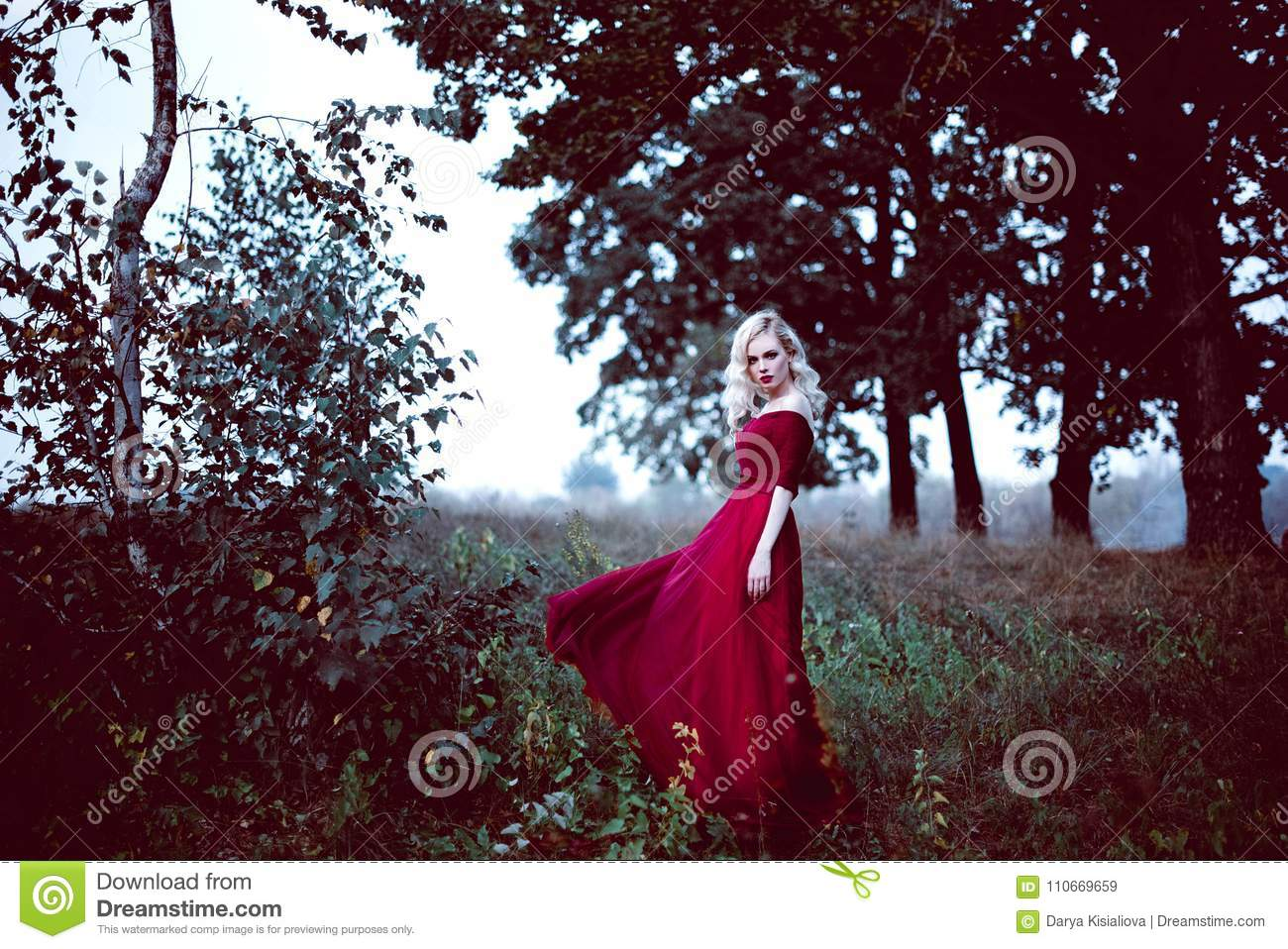 Fashion gorgeous young blonde woman in beautiful red dress in a fairy-tale forest. magic atmosphere. Retouched toning shot