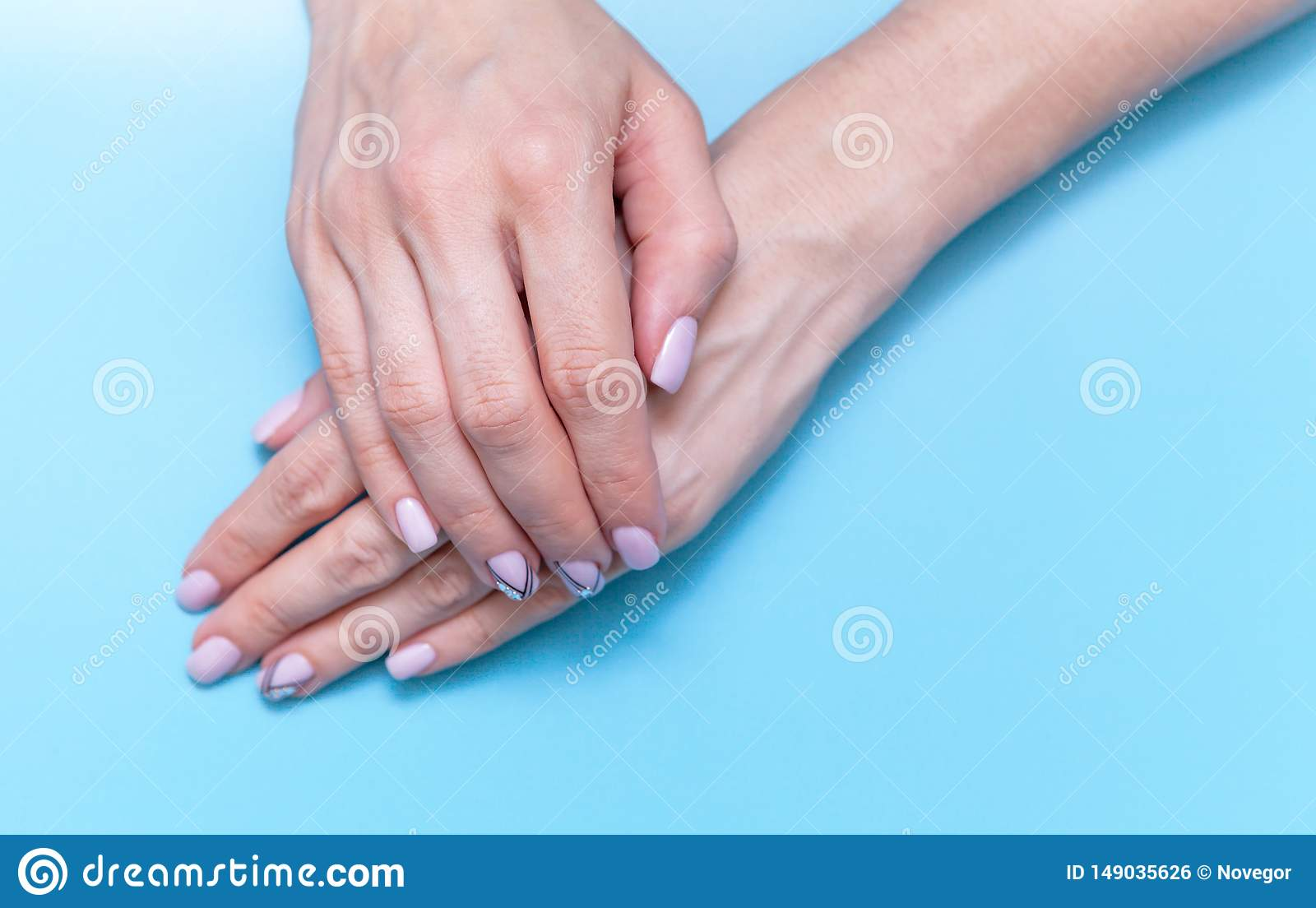 Fashion hand art women, hand with bright contrast makeup and beautiful nails, hand care. Creative beauty photo girl on blue