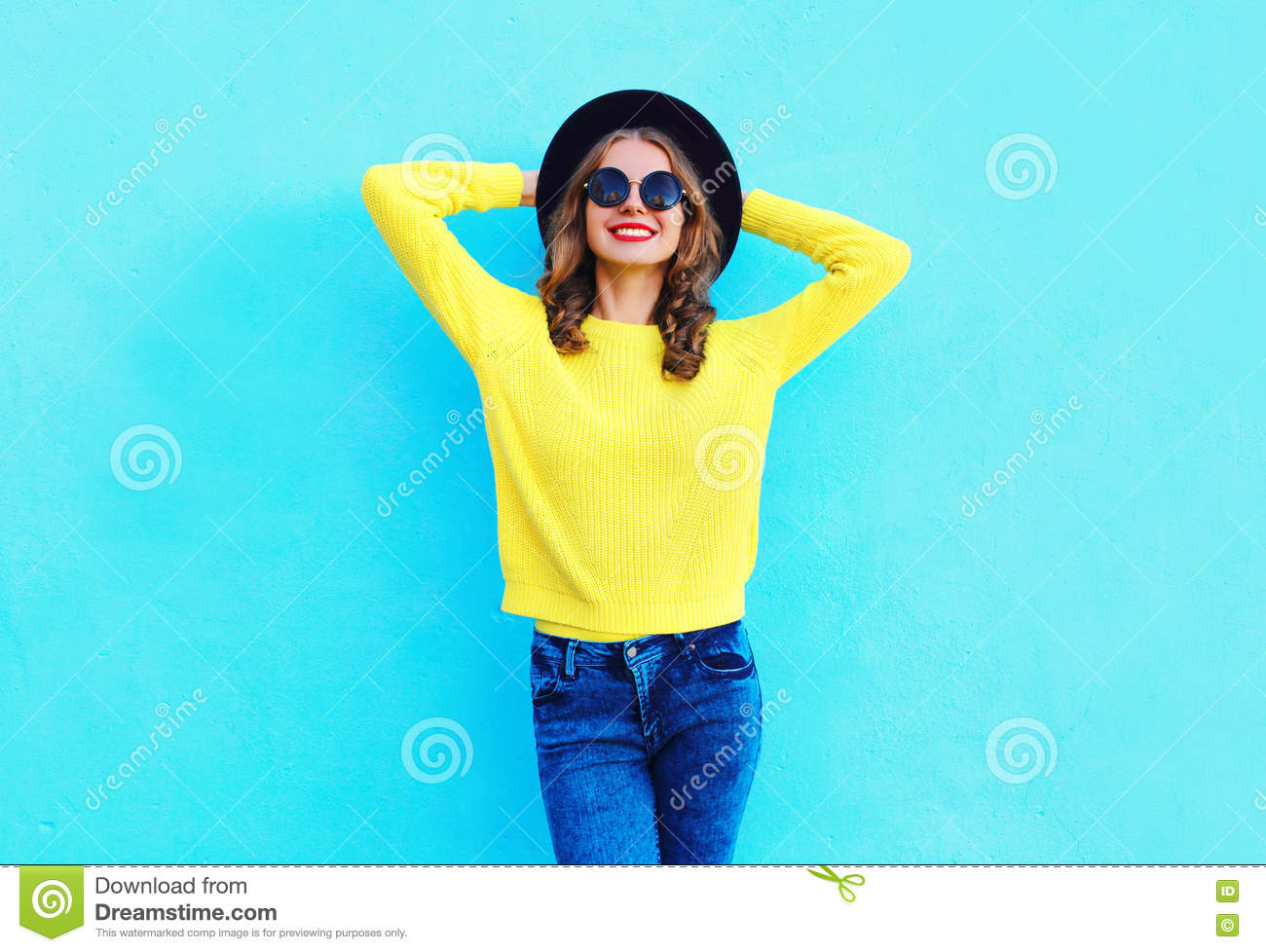Fashion happy pretty smiling woman wearing a black hat and yellow knitted sweater over colorful blue