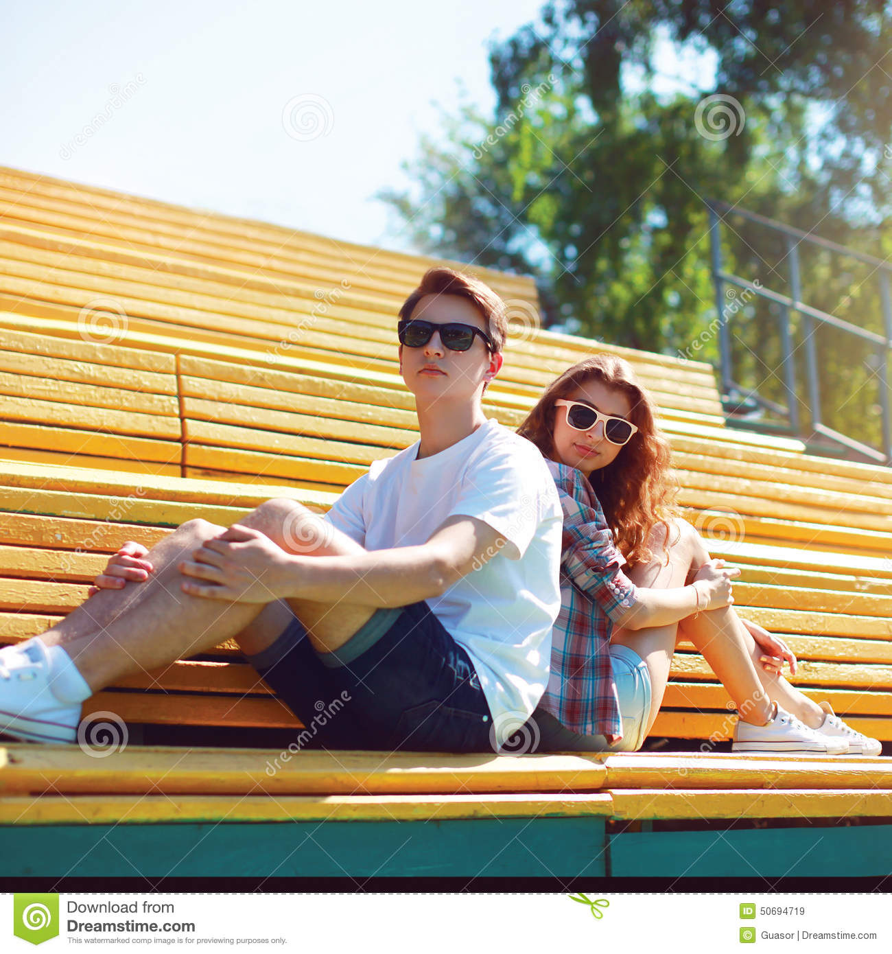 Fashion Hipster Couple In Sunglasses Sitting On The Bench