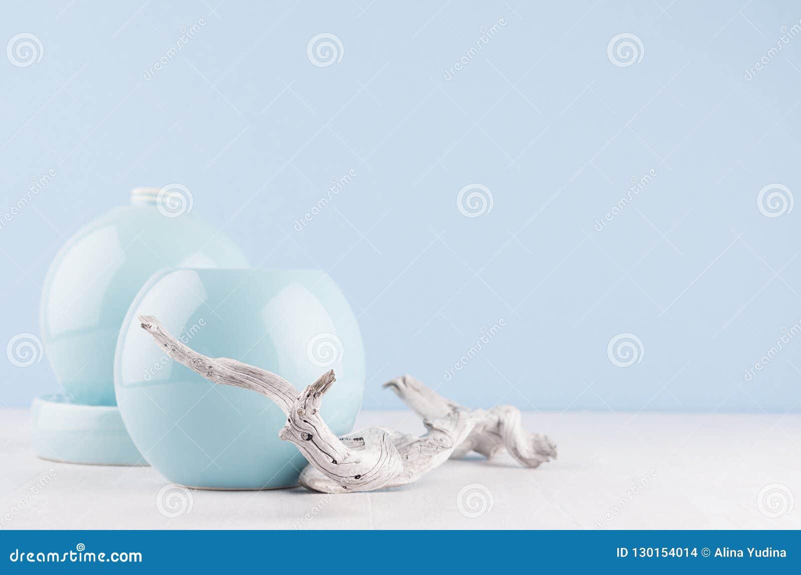 Fashion home decor in modern elegant japanese style - light soft blue ceramic vases and old shabby branch on white wood background