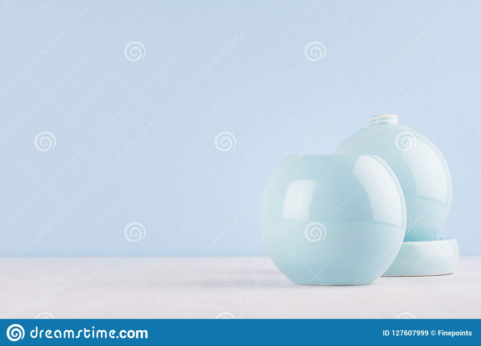 Fashion home decor in modern elegant style - light soft blue ceramic circle vases on white wood background.