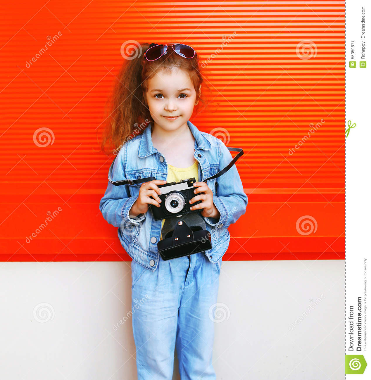defd00623f18 Fashion kid concept - portrait of stylish little girl child wearing a jeans  clothes and sunglasses with old retro vintage camera against the colorful  red ...