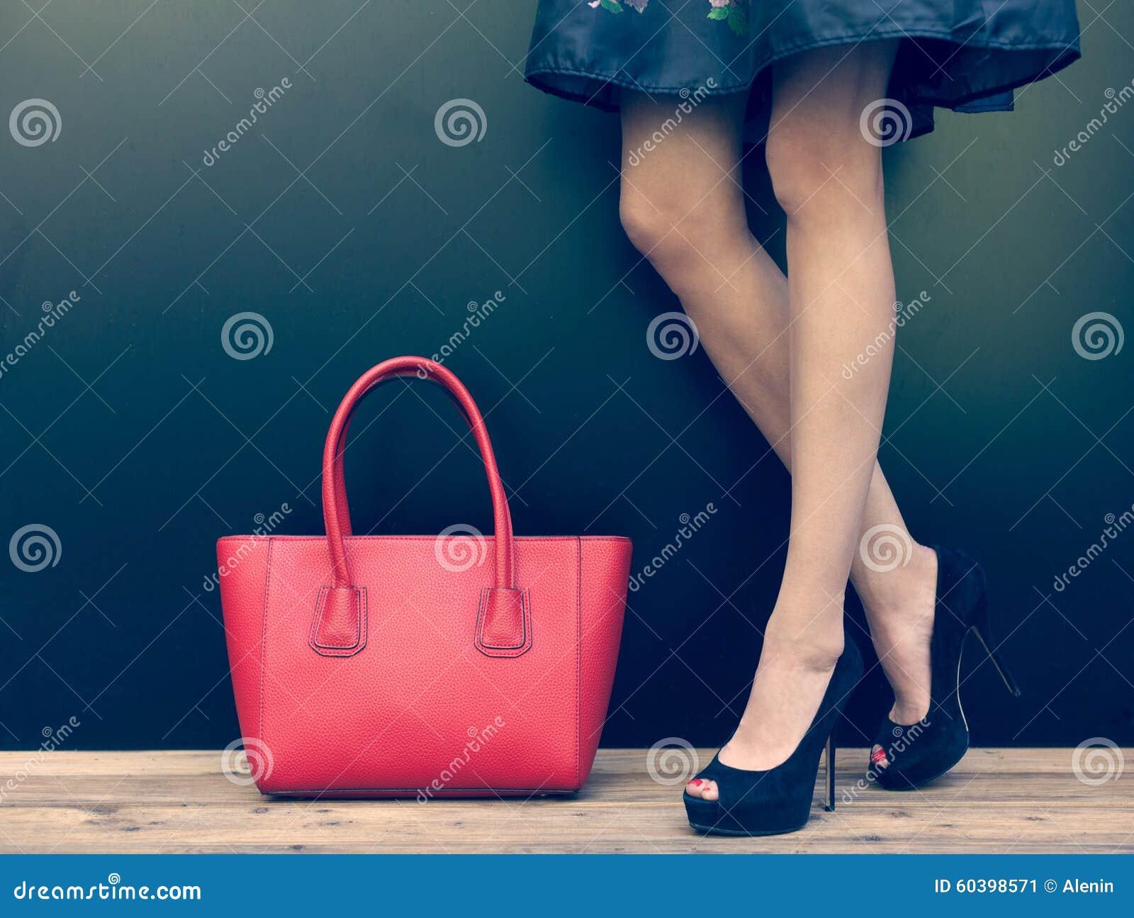 7a28fdd0668 Fashion leggy girl in a beautiful high-heeled shoes in short denim dress  summer posing near the dark wall. Close-up.