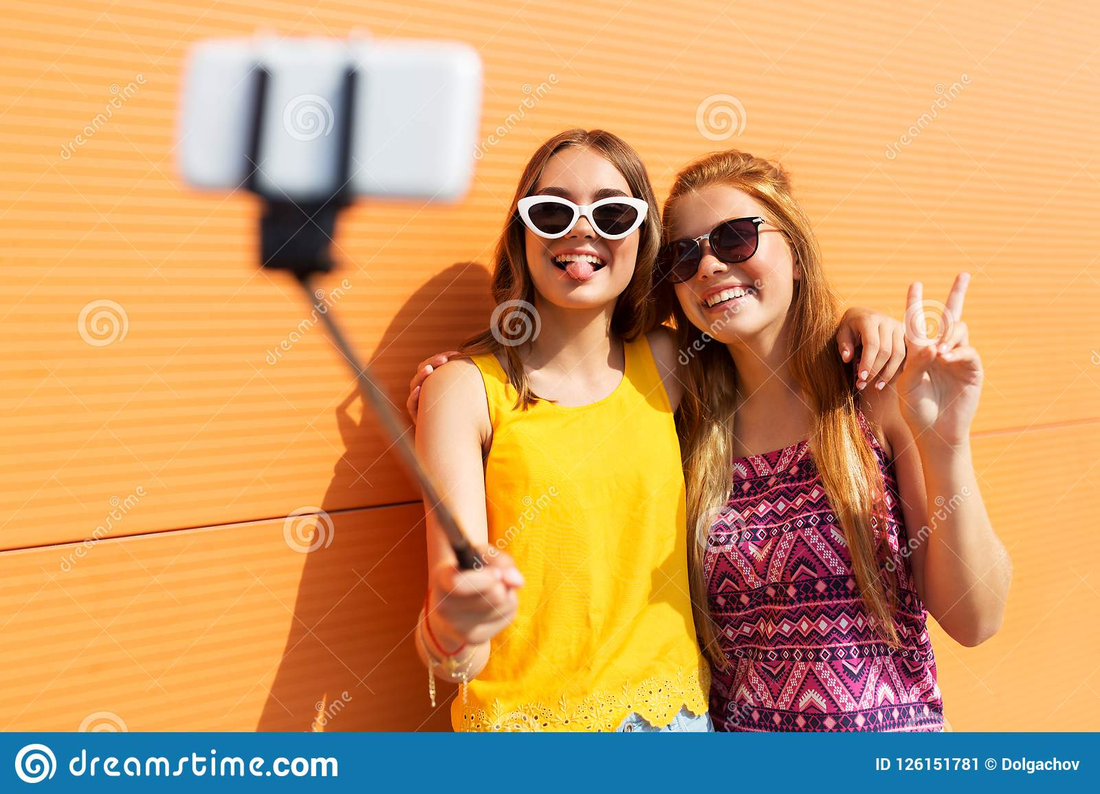 Teenage girls taking picture by selfie stick