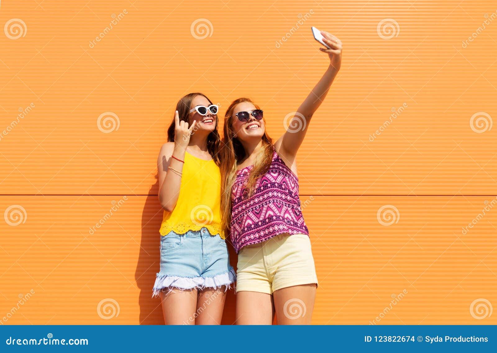 Teen girls taking selfie by smartphone in summer
