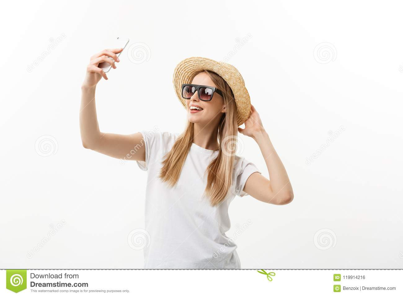 Fashion and Lifestyle Concept: pretty young woman wearing a hat, sunglasses takeing a photo of herself by mobile phone