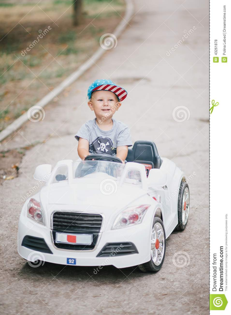 Little Boy With Toy Car : Fashion little boy driving toy car in a park stock photo