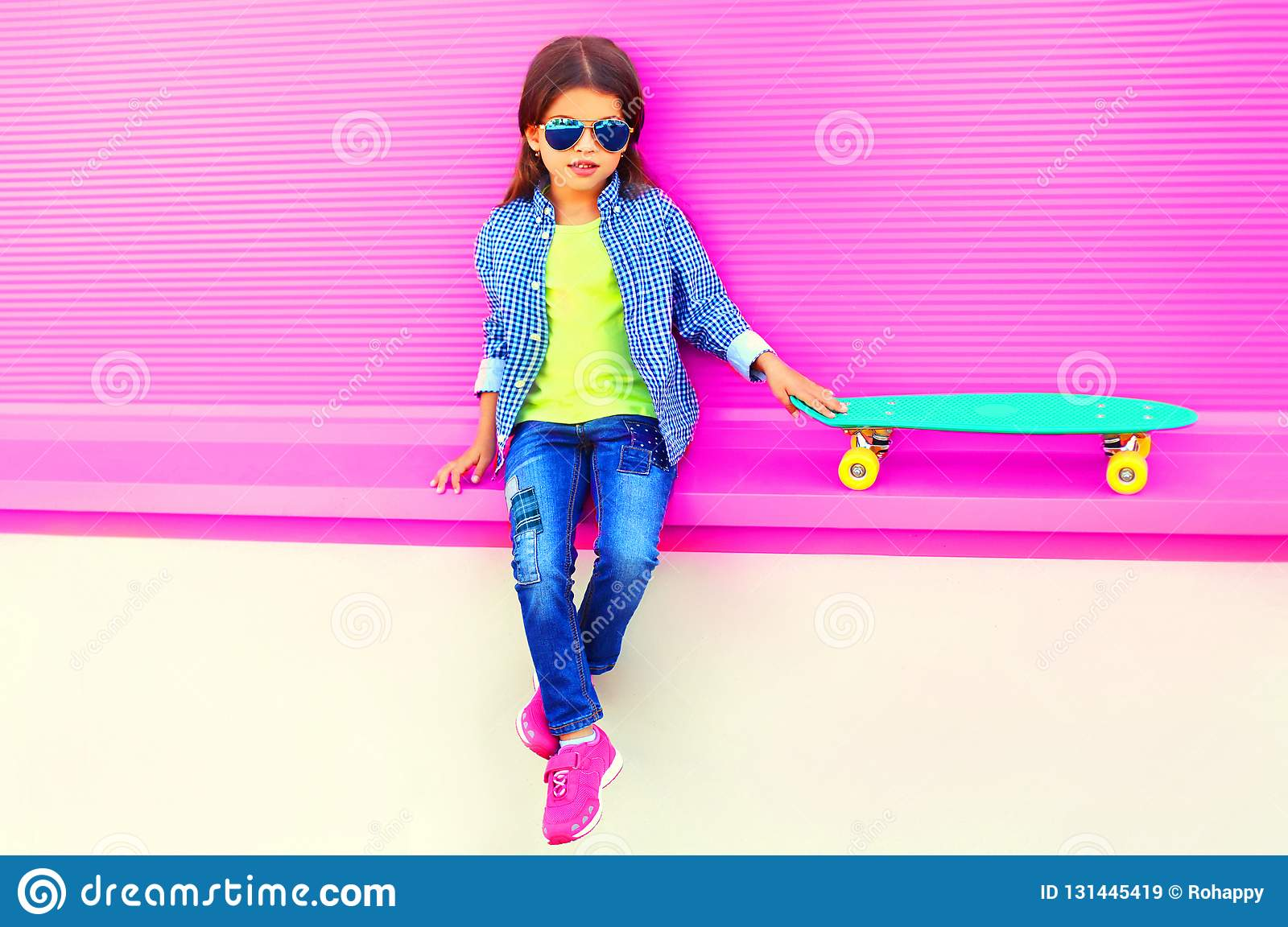 Fashion little girl child sitting with skateboard in city on colorful pink wall