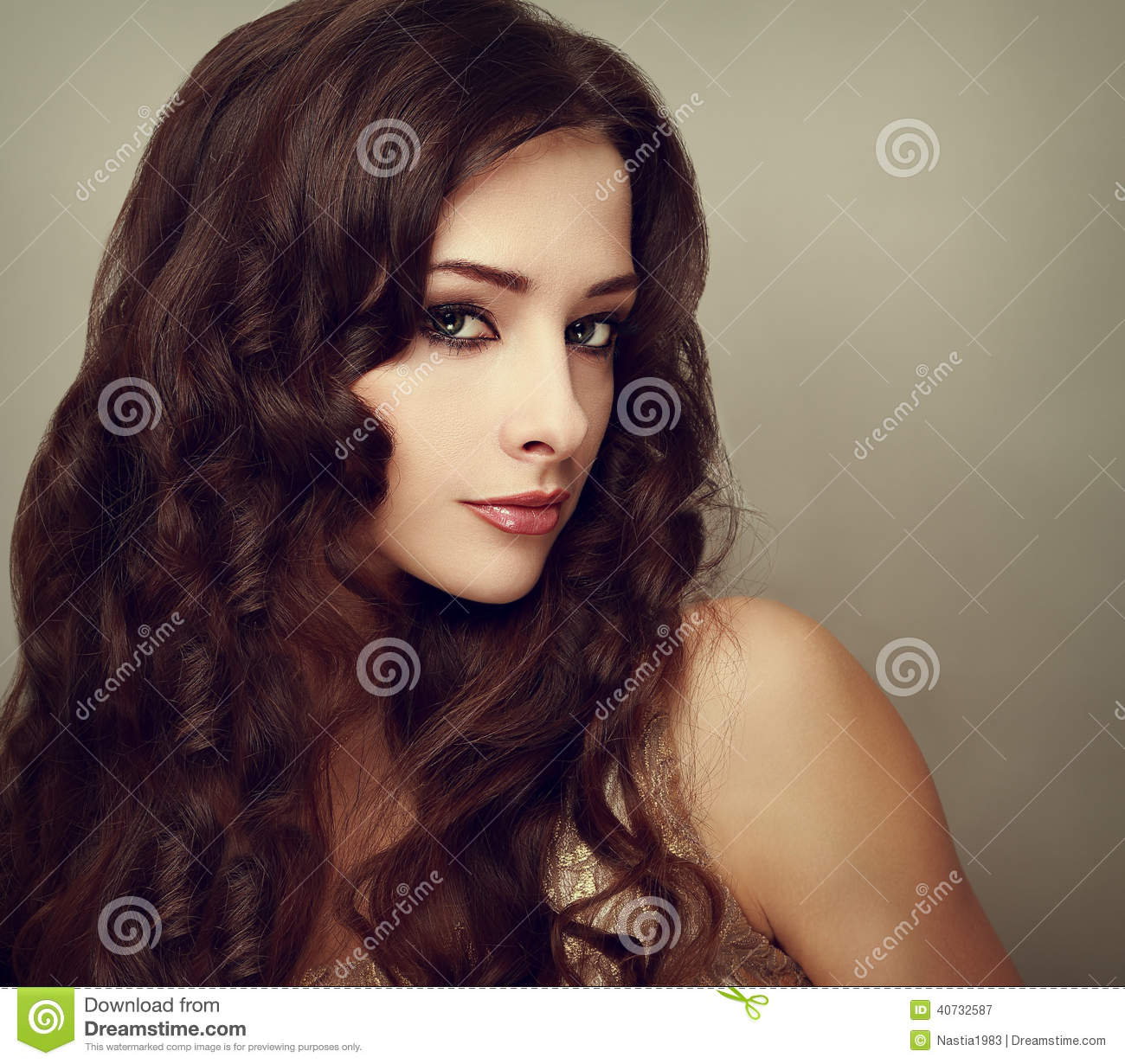 Fashion luxury female model with long curly hair. Vogue