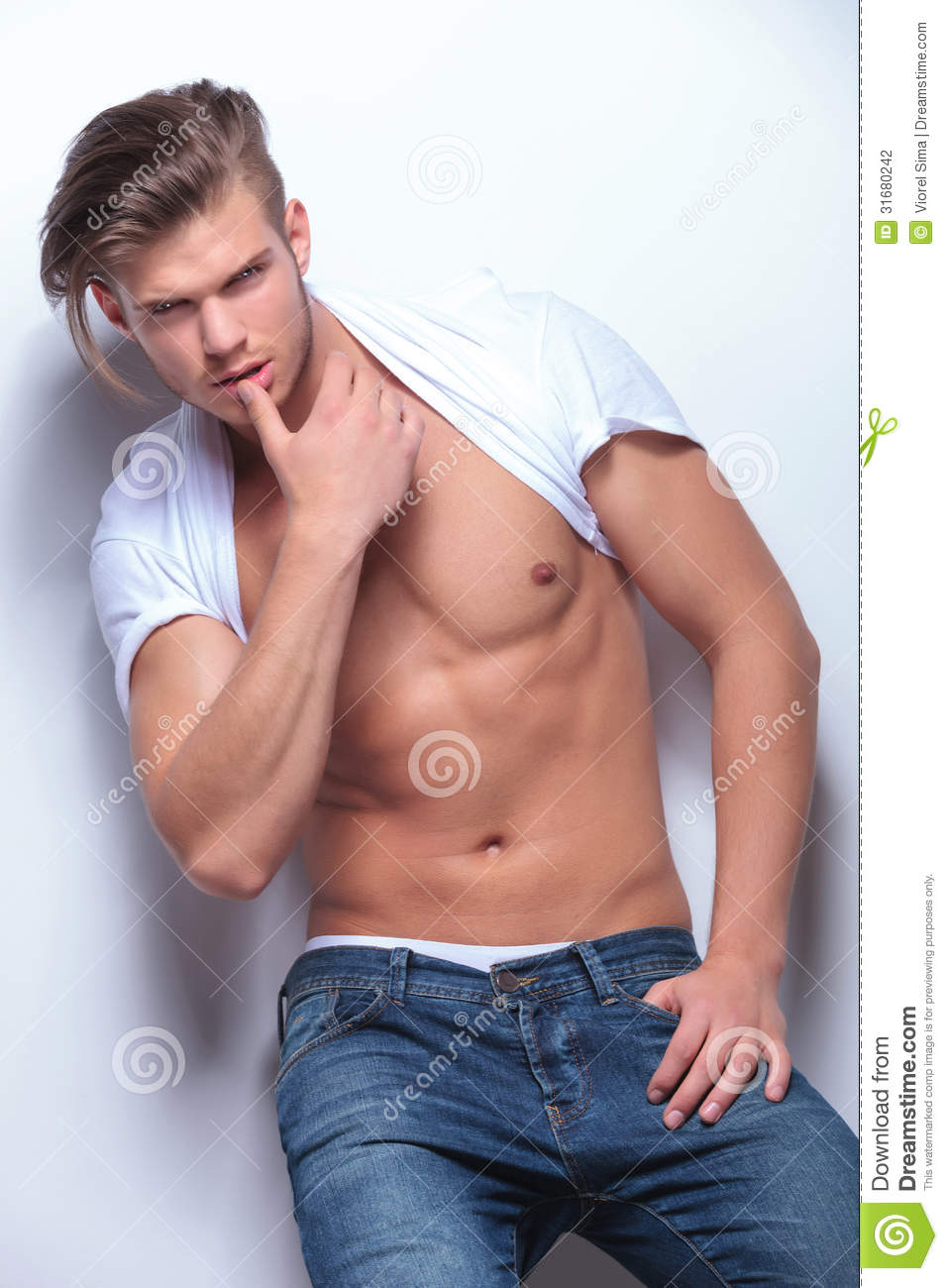 fashion-man-touches-his-lip-young-t-shirt-pulled-over-neck-revealing-big-musculature-touching-lower-thumb-light-31680242.jpg