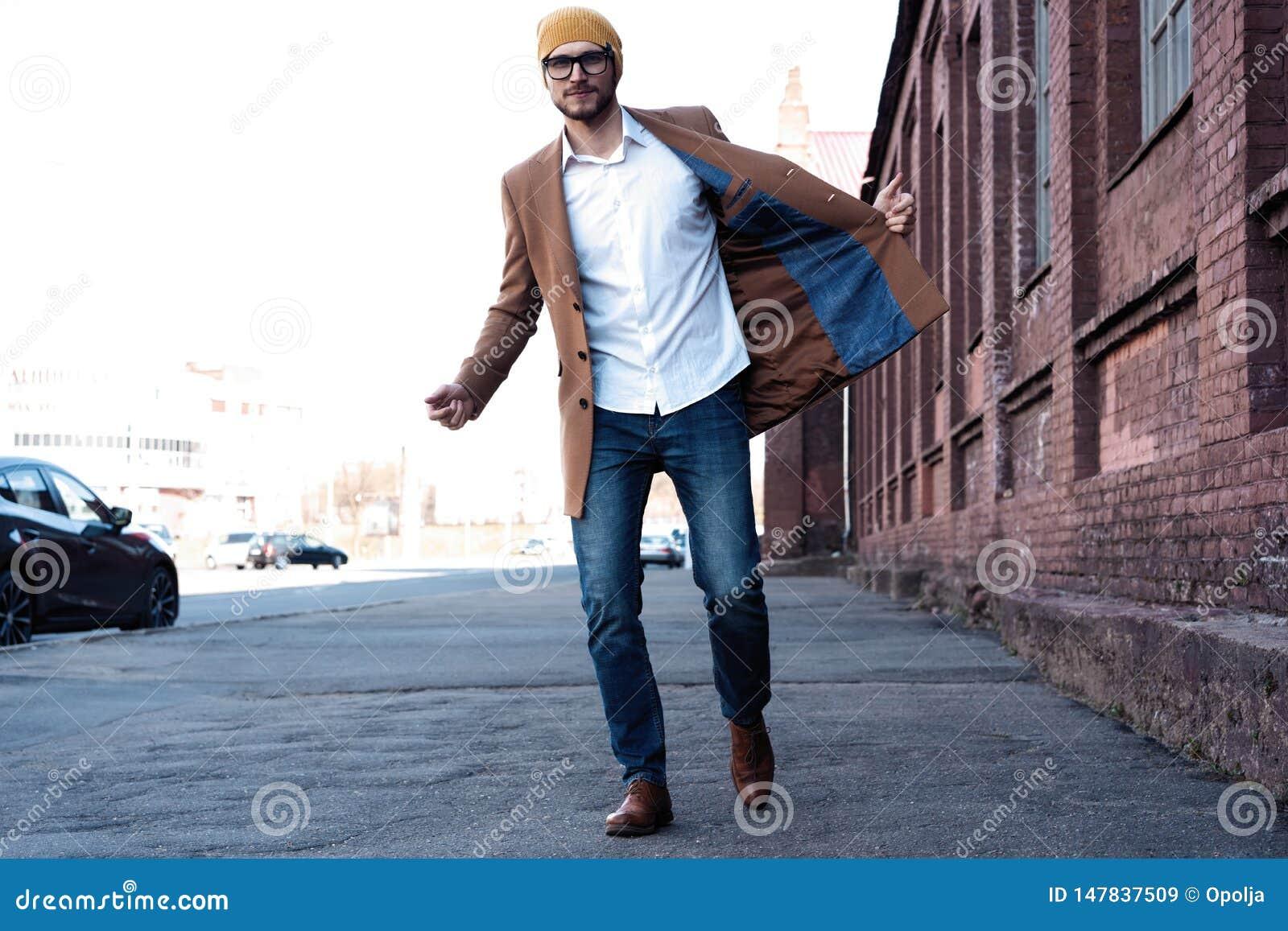 Fashion manst?enden Ung man i exponeringsglas som b?r laget som g?r ner gatan