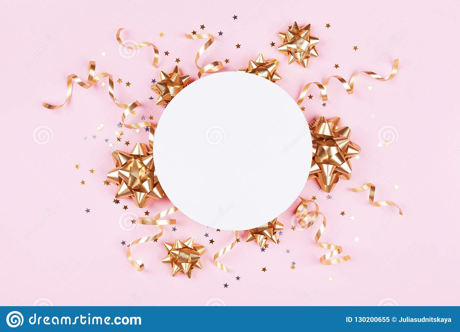 Fashion mockup with golden bows, serpentine and star confetti on pink pastel table top view. Flat lay for birthday or christmas.
