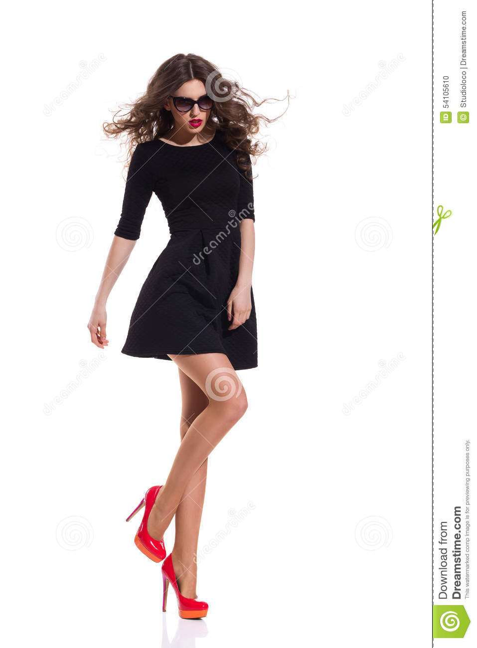 3901cb743d2d Beautiful woman in sunglasses wearing black mini dress and red high heels  standing on one leg. Full length studio shot isolated on white.