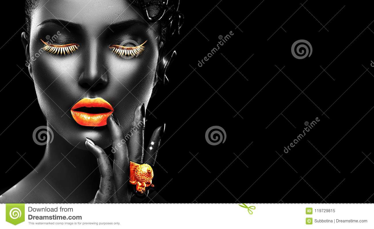 Fashion model with black skin, golden lips, eyelashes and jewellery - golden ring on hand. on black background