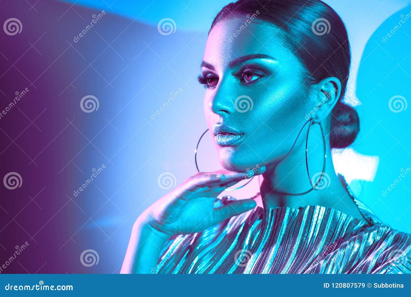 Fashion model brunette woman in colorful bright neon lights. Beautiful girl, trendy glowing makeup, metallic silver lips
