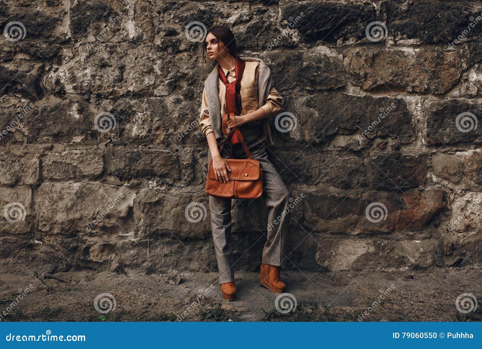 Fashion Model In Fashionable Clothes. Beautiful Woman Near Wall