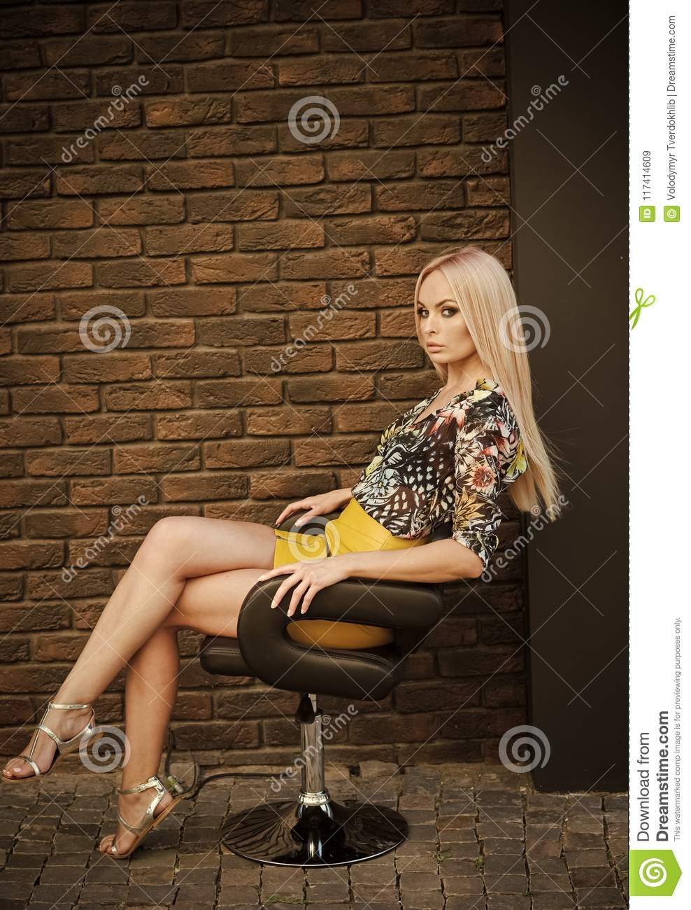Fashion model in fashionable clothes sit in armchair. woman has her style, vogue. Woman with long blond hair and