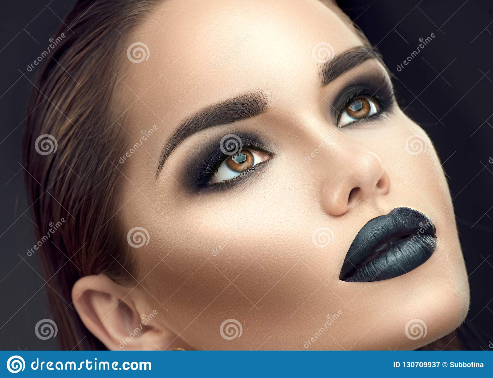 Fashion model girl portrait with trendy gothic black makeup. Young woman with black lipstick, dark smokey eyes, face contouring, beauty eyebrows