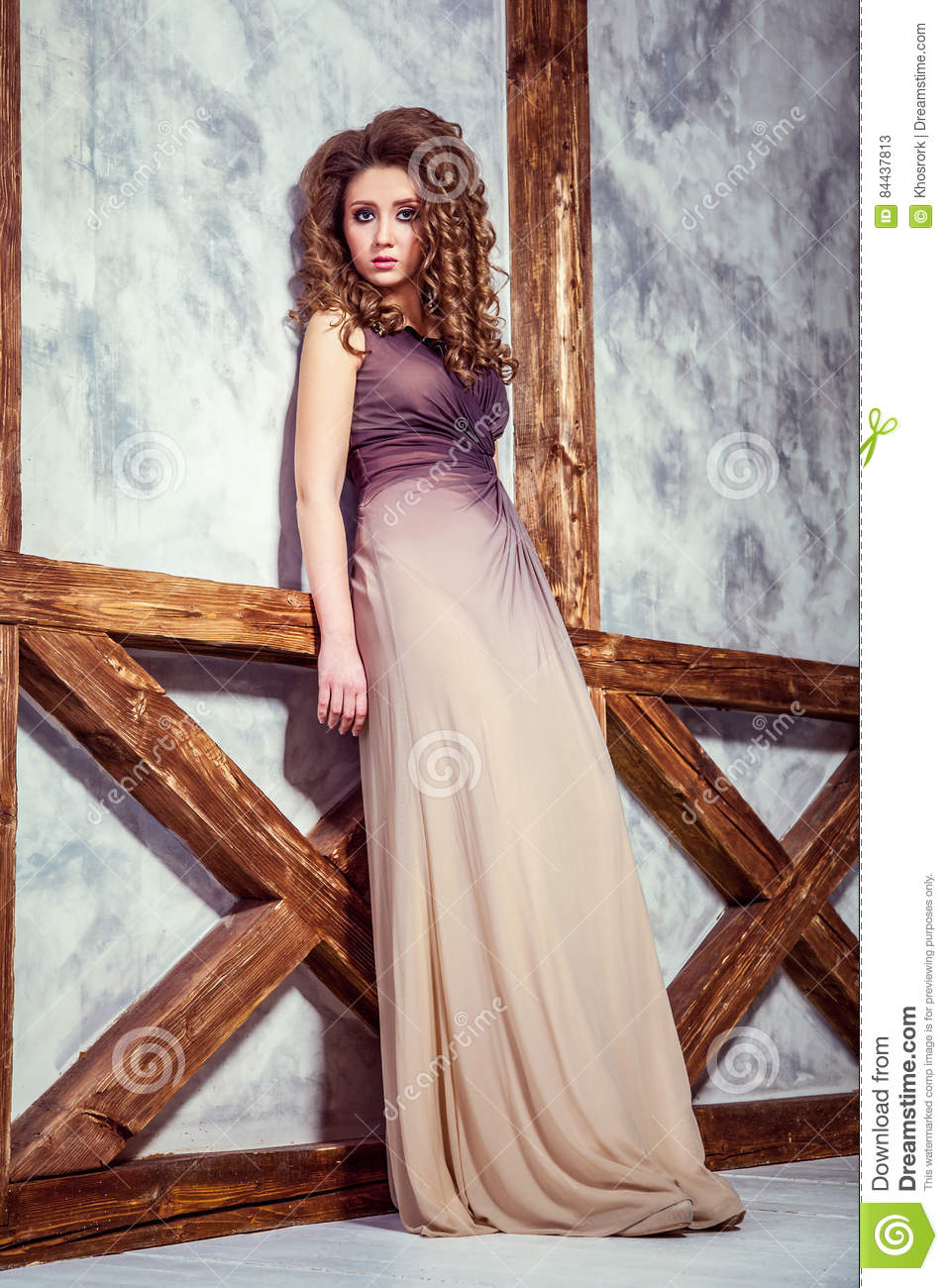 Fashion Model With Long Dress And Curly Hairstyle And Makeup Posing Near Wall With Wooden Pole Stock Image Image Of Long Accessories 84437813