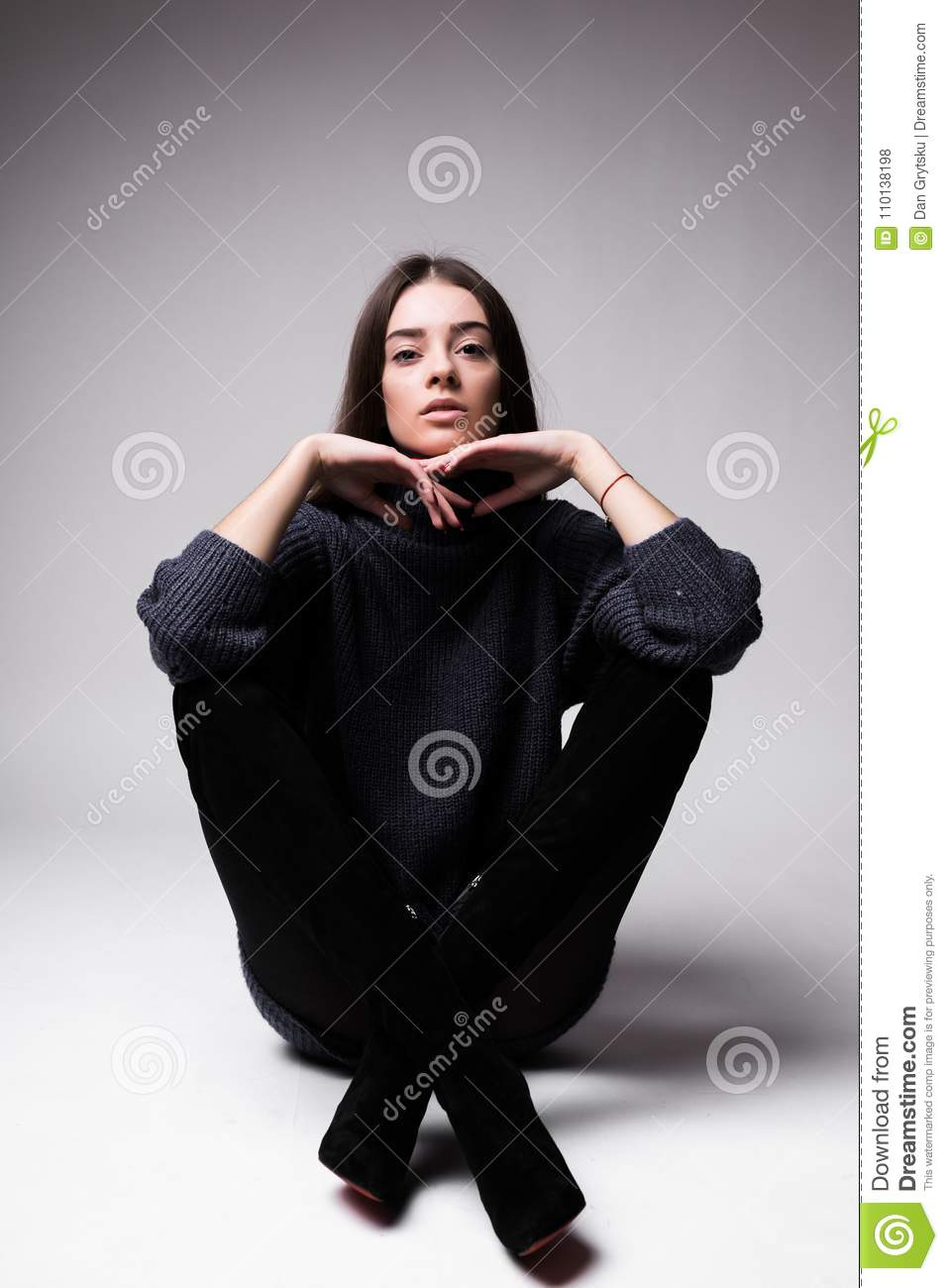 Fashion model woman in modern clothes sitting on the floor isolated on white background