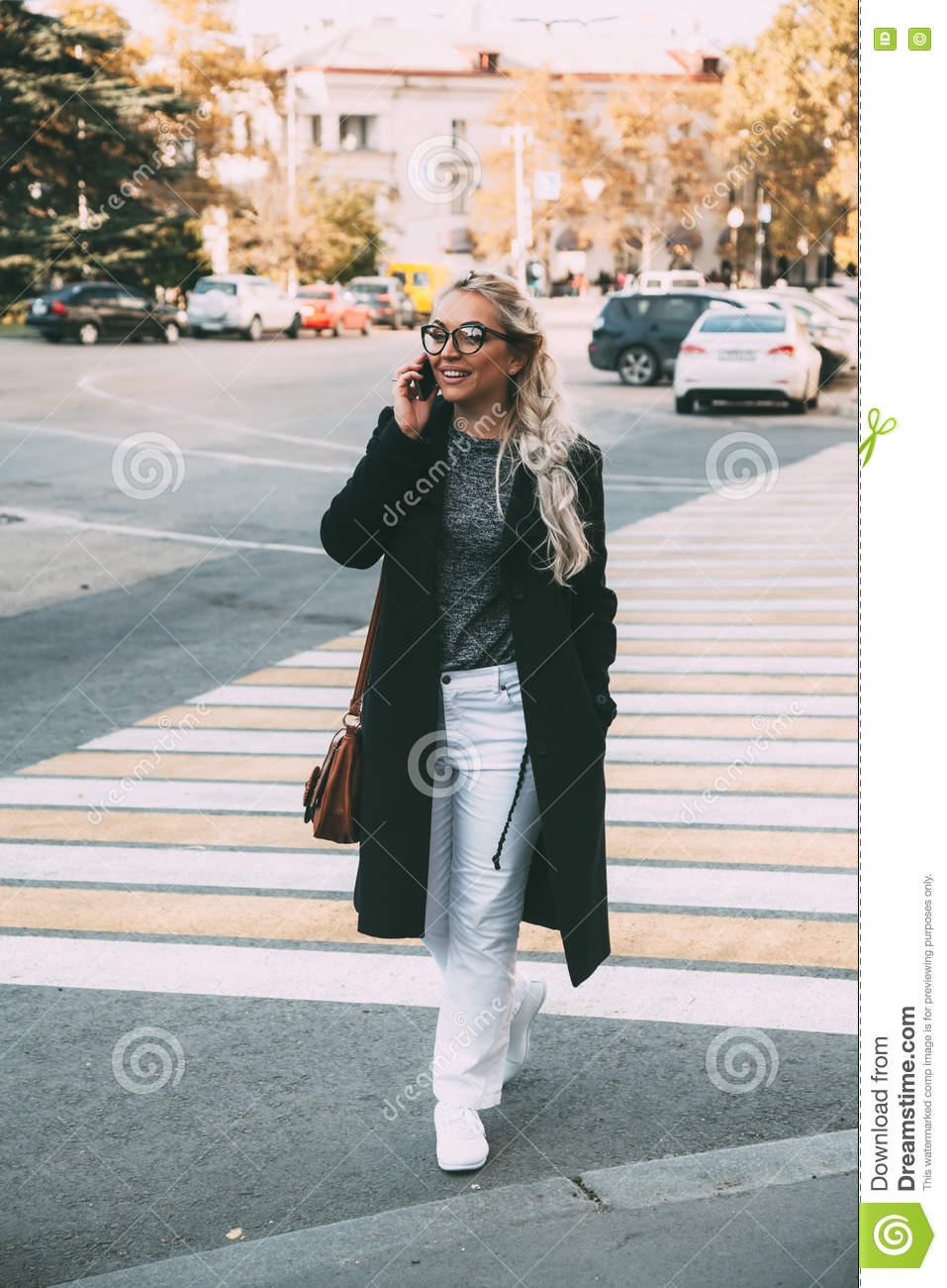 865f1c4f0505 ... hipster glasses walking on the city street and talking by phone on  crosswalk. Fall casual fashion, elegant everyday look. size model,  lifestyle photo.