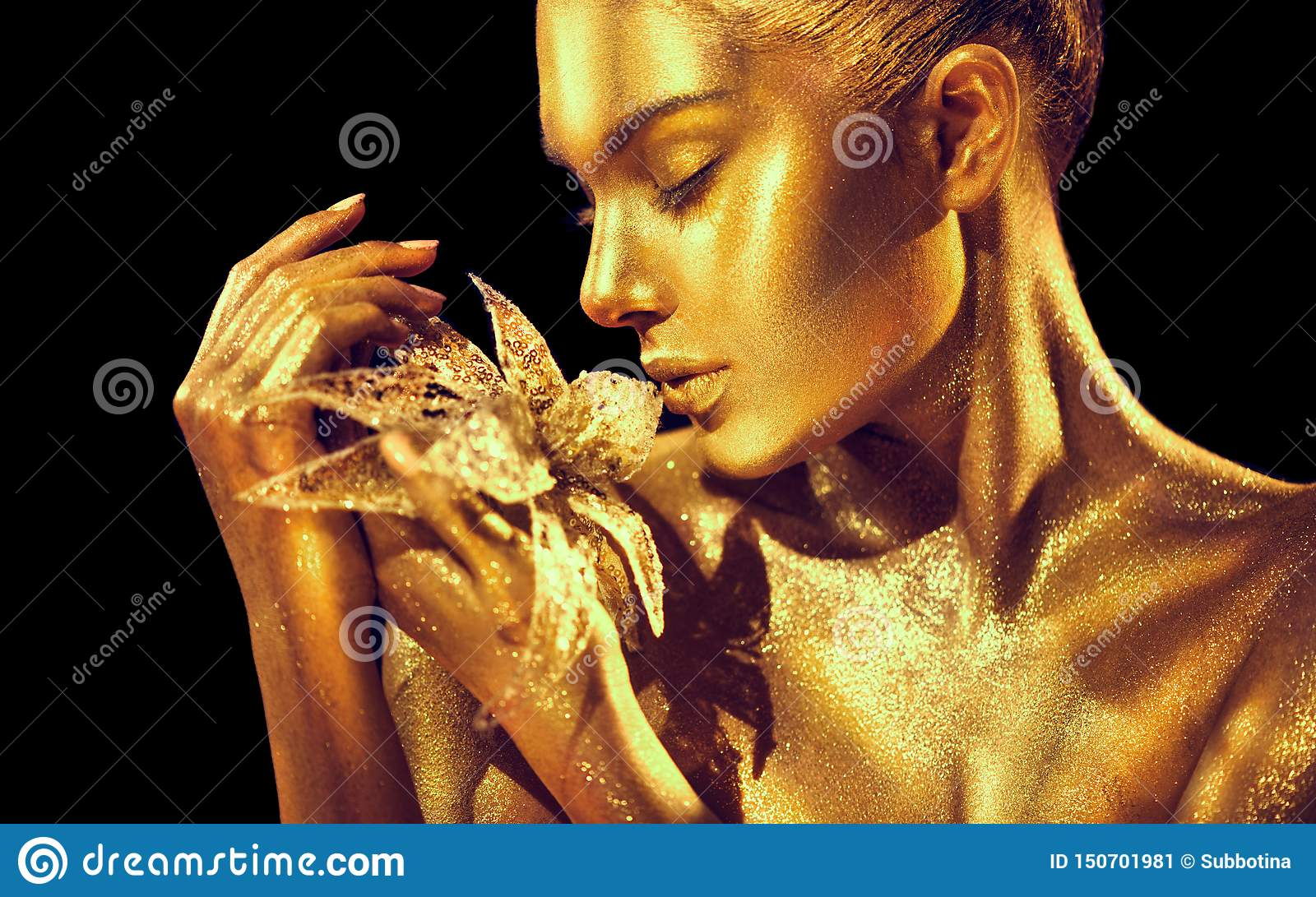 Fashion model woman with bright golden sparkles on skin posing, fantasy flower. Portrait of beautiful girl with glowing makeup