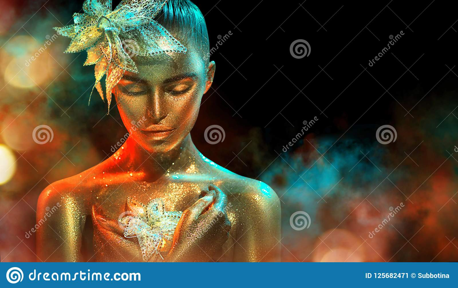 Fashion model woman in colorful bright golden sparkles and neon lights posing with fantasy flower. Portrait of beautiful girl