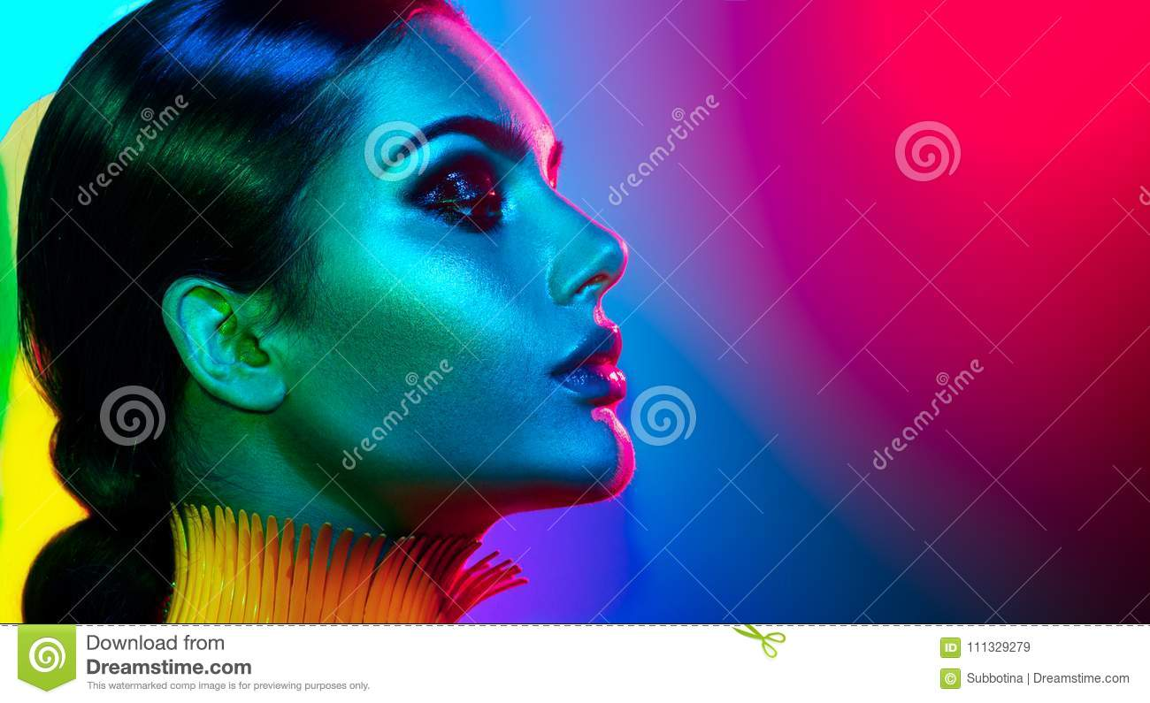 Fashion model woman in colorful bright lights posing. Portrait of girl with trendy makeup