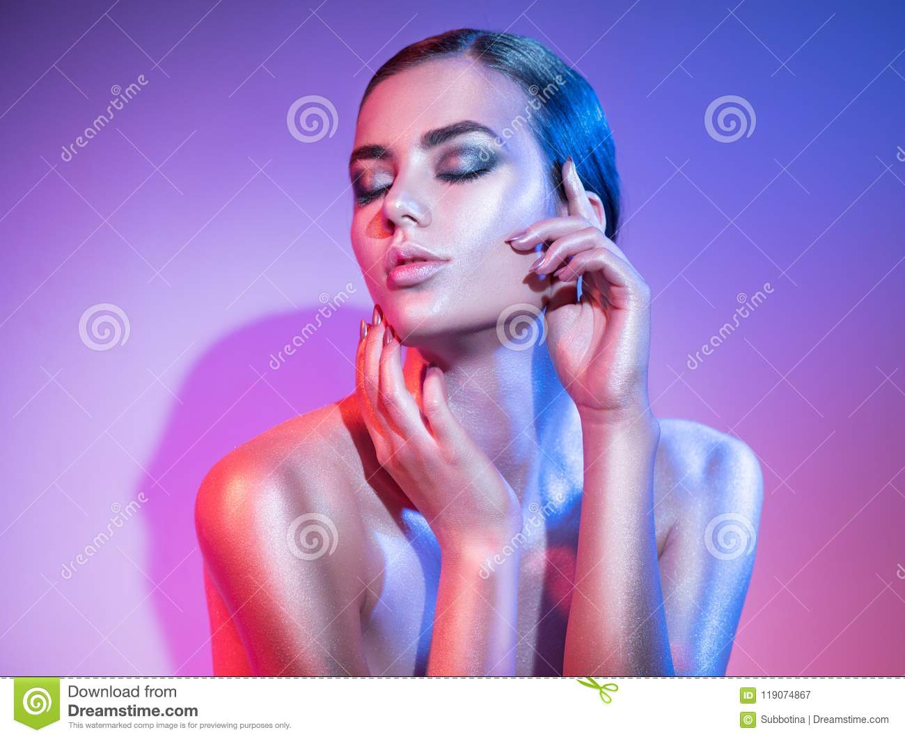 Fashion model woman in colourful bright sparkles and neon lights posing in studio, portrait of beautiful girl