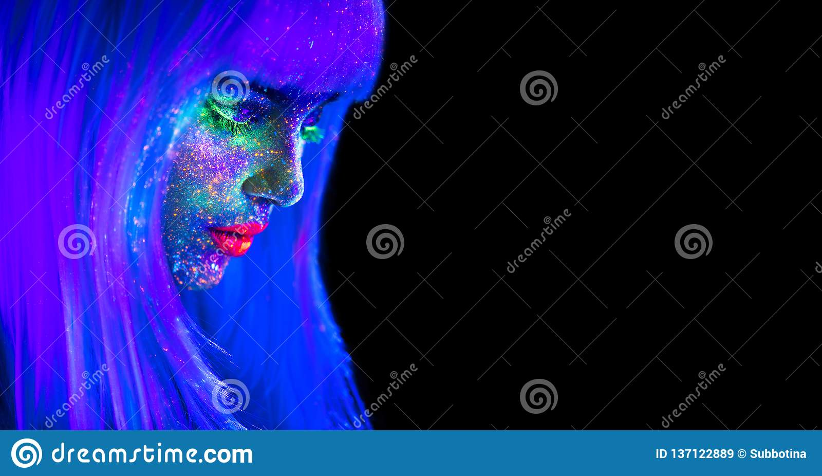 Fashion model woman in neon light. Beautiful model girl with colorful bright fluorescent makeup isolated on black. Ultraviolet
