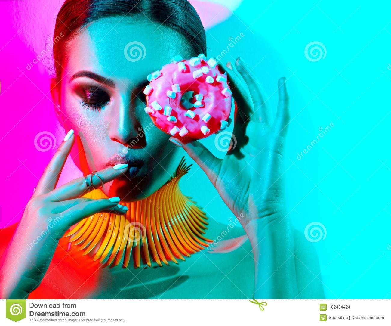 Fashion model woman posing in studio with donut