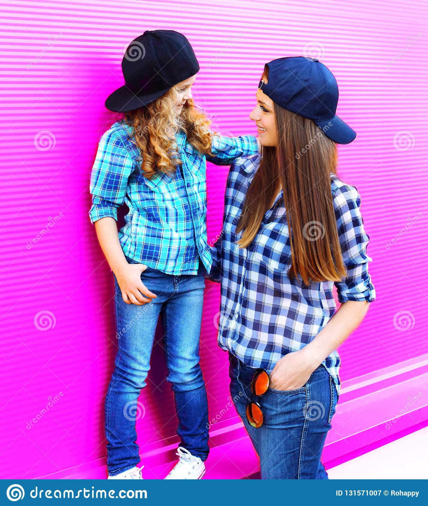 Fashion mother looking at child little girl in checkered shirts and baseball caps in city on colorful pink wall