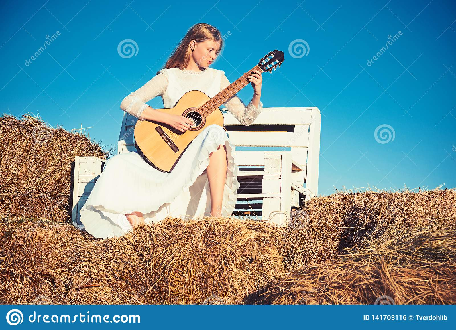 Fashion musician in white dress on sunny nature. Woman guitarist perform music concert. Albino girl hold acoustic guitar