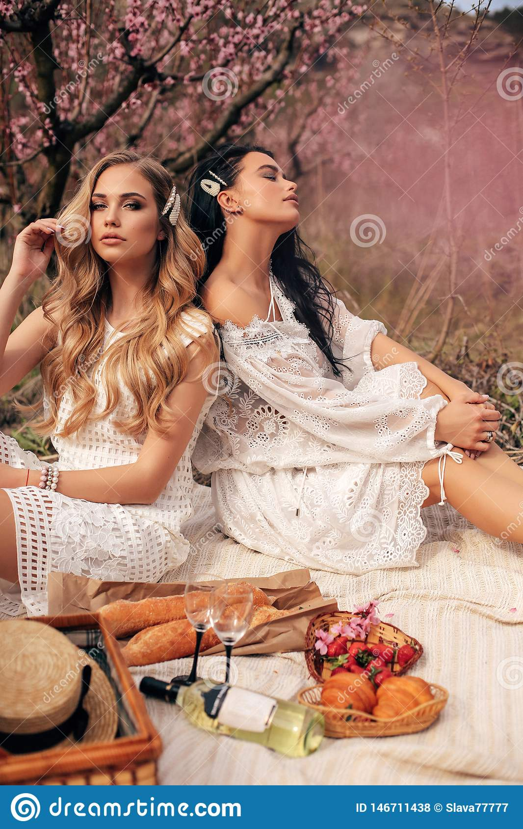 Beautiful girls in elegant dresses having romantic picnic among flowering peach trees in garden