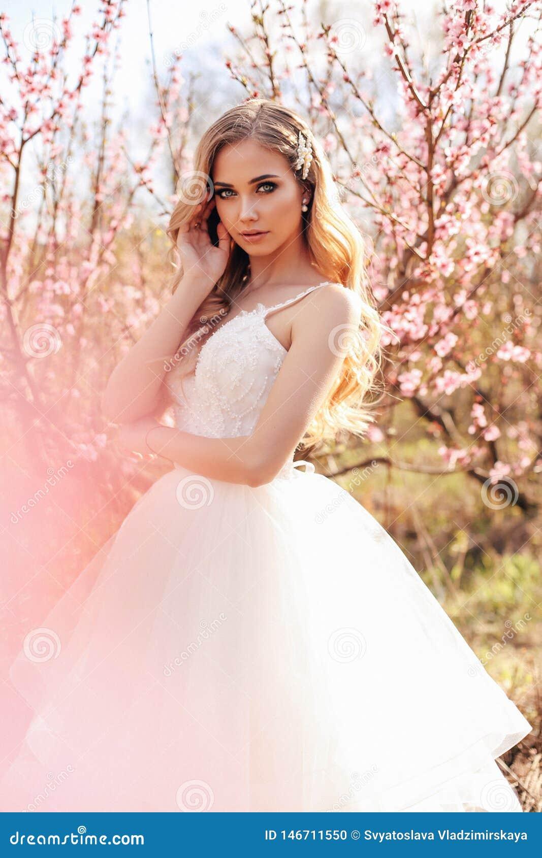 Beautiful Girl With Blond Hair In Elegant Wedding Dress Posing