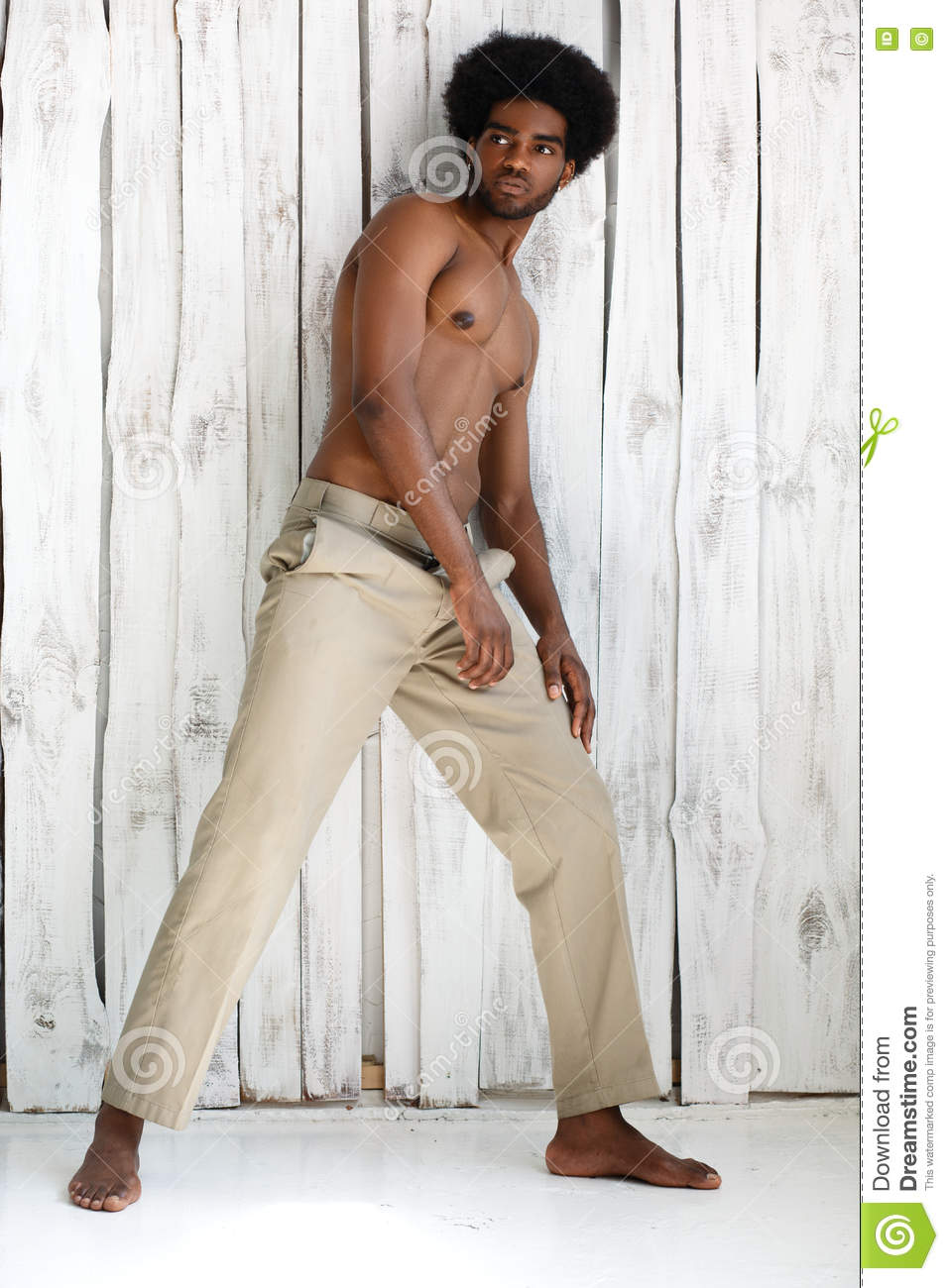 Fashion photo of african american athletic man with sport wet body is posing near the texture wall background