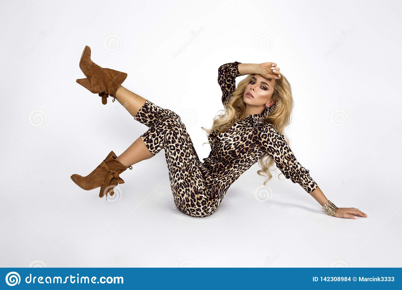 Fashion photo of a beautiful elegant young woman in a pretty jumpsuit with leopard animal print and boots posing over white
