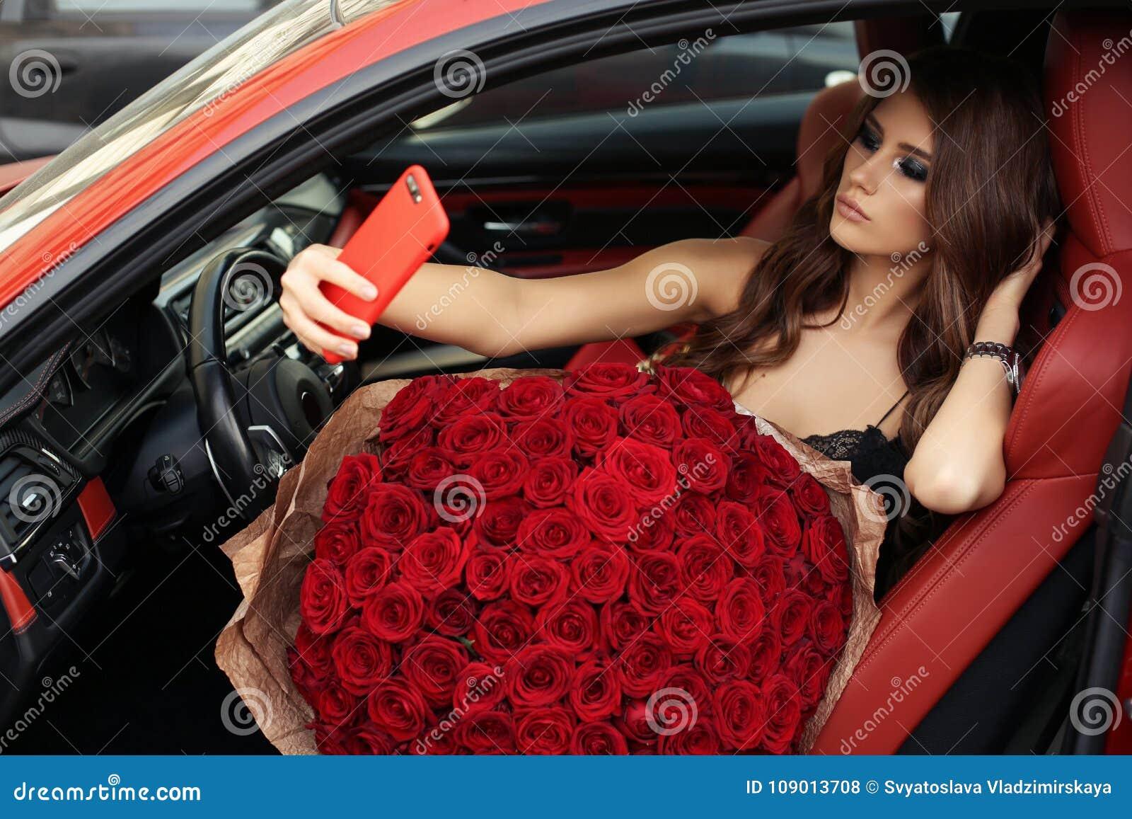 Beautiful girl in elegant dress posing in luxurious car with bo