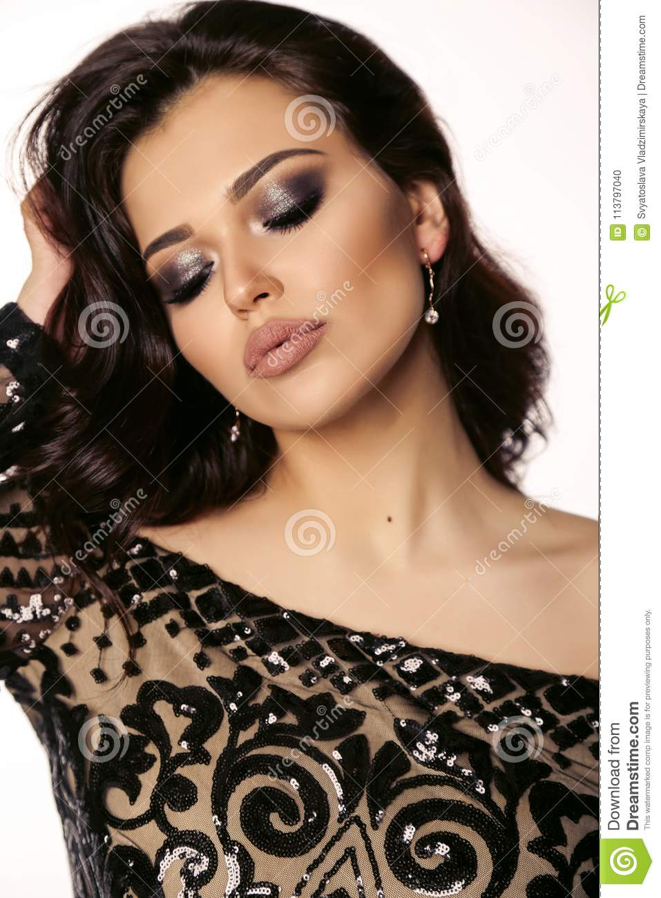 Beautiful girl with dark hair and evening makeup in luxurious bl