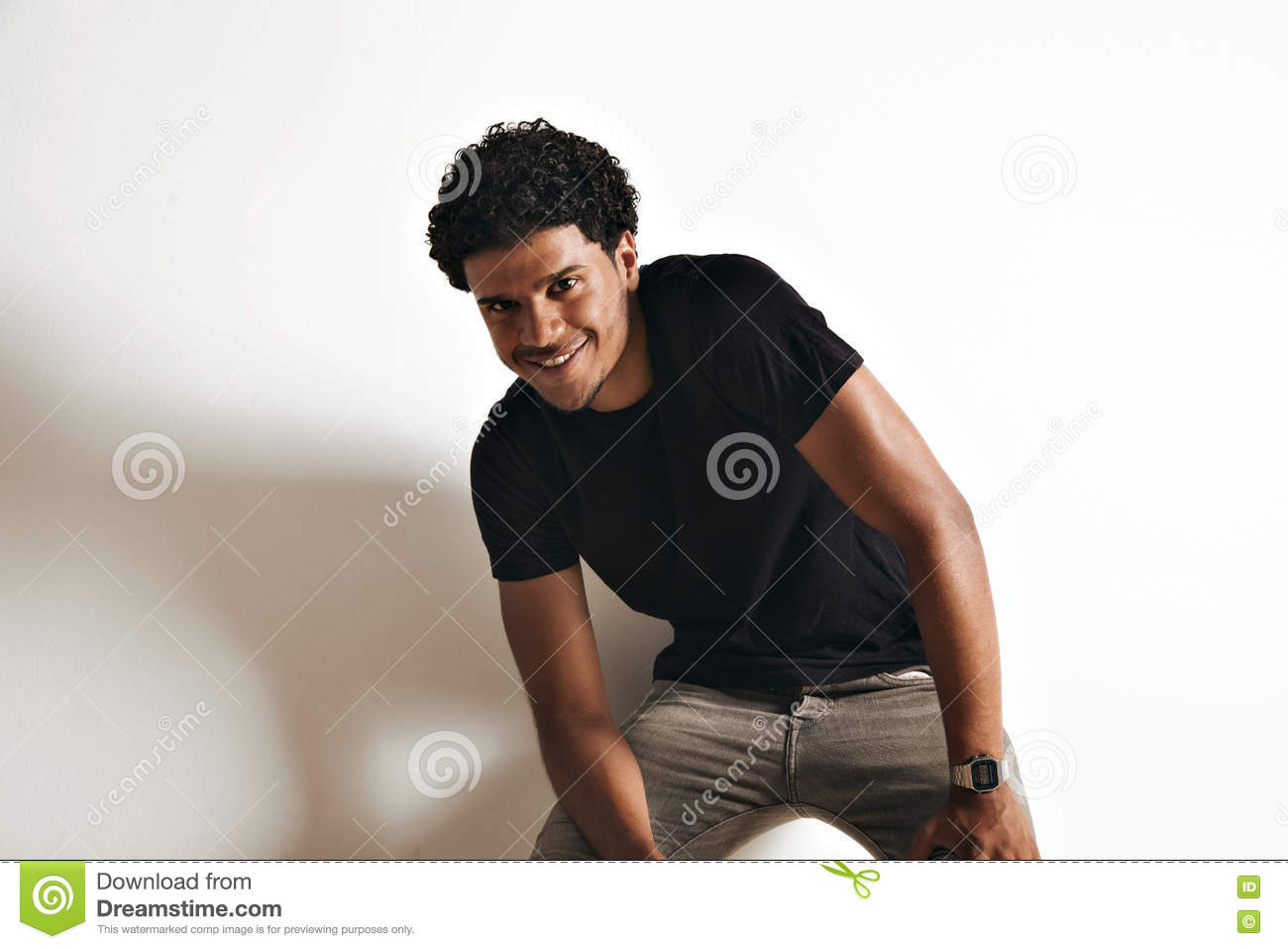 Playful in motion photo of a smiling black young man in a plain black cotton t shirt and grey jeans against white wall background