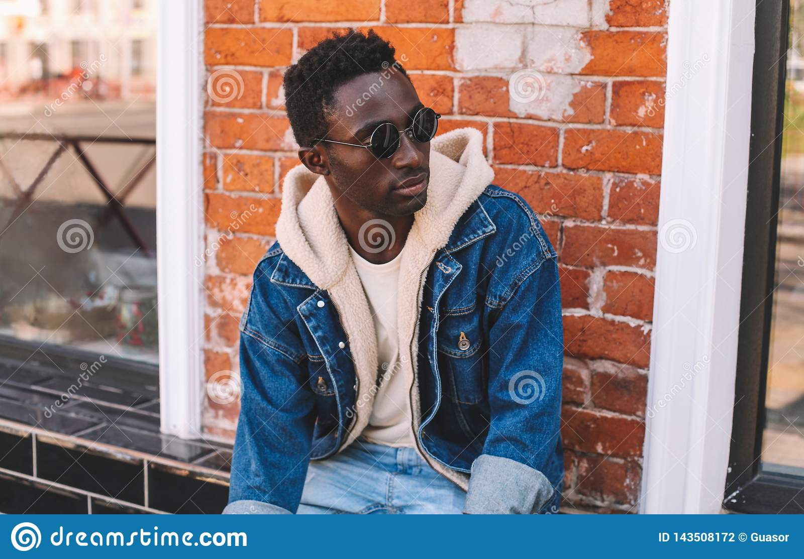 Fashion portrait african man wearing jeans jacket sitting on city street over brick textured wall